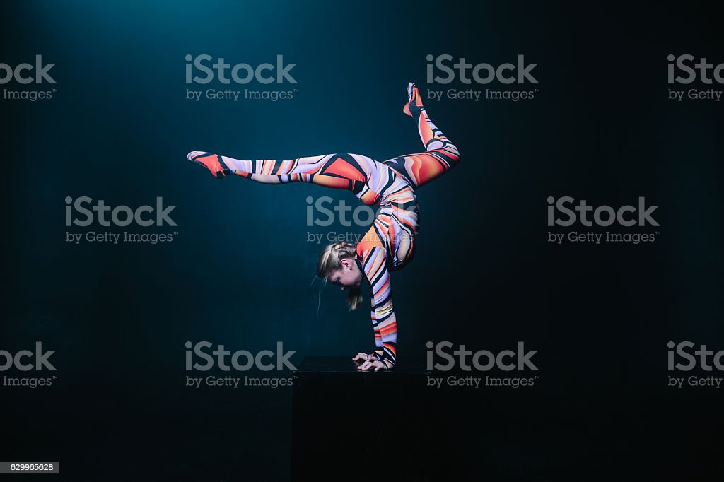 Flexible blonde circus acrobat doing equilibre balance handstand stock photo