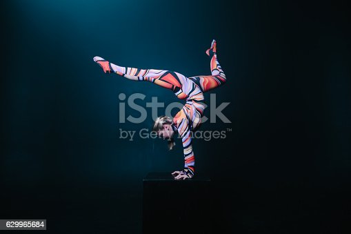 istock Flexible circus acrobat doing equilibre balance handstand on a cube. 629965684