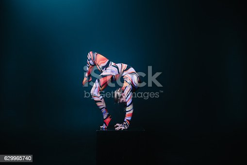 istock Flexible circus acrobat doing equilibre balance handstand on a cube. 629965740
