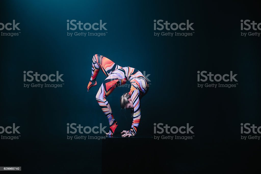 Flexible circus acrobat doing equilibre balance handstand on a cube. stock photo