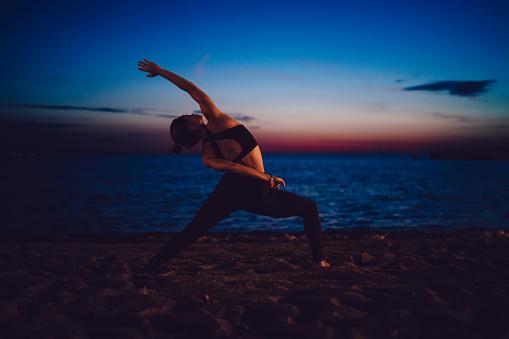 Flexible female yogi practicing hatha on evening seashore beach stretching body muscles for keeping perfect slim figure, fit girl enjoying nature inspiration during pilates training at coastline