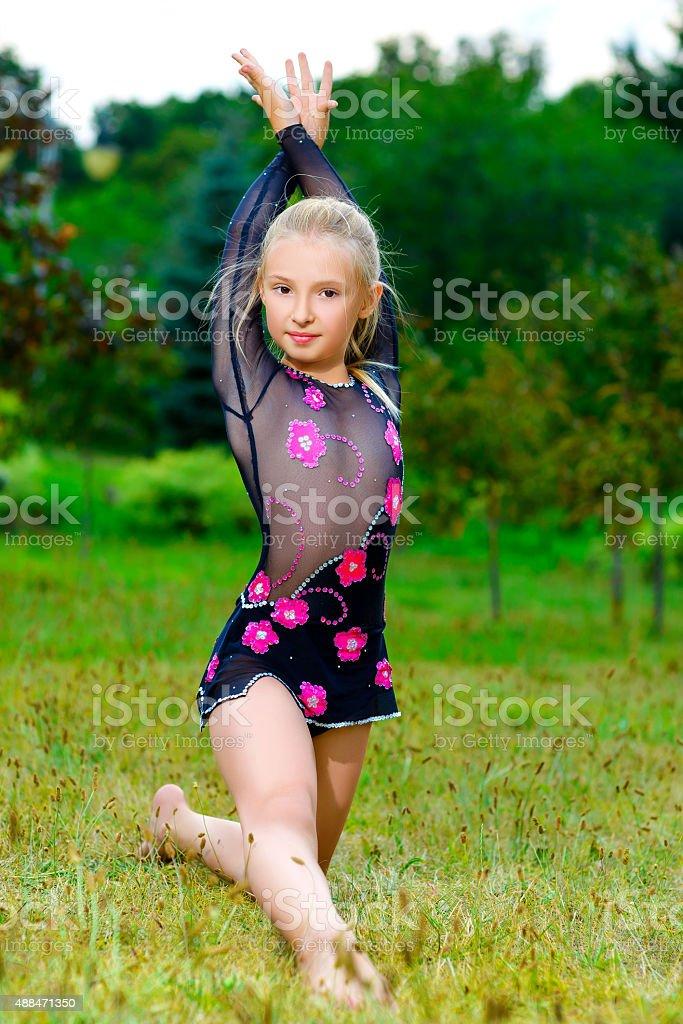 flexible little girl doing gymnastics vertical split with
