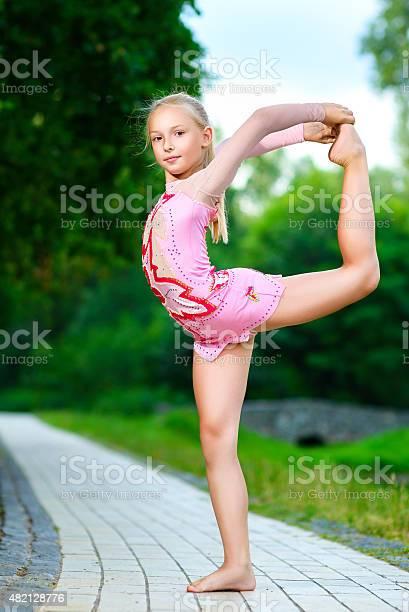 Flexible Skinny Girl Posing In Vertical Split Stock Photo