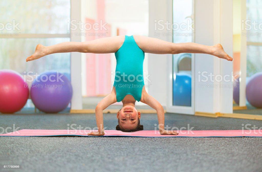 Flexible Little Girl Gymnast Standing On Head In Gym Stockfoto und ...