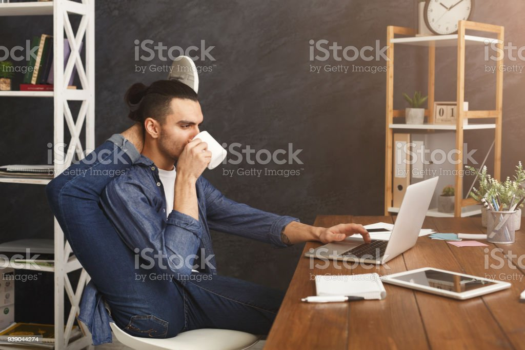 Flexible man practicing yoga at workplace stock photo