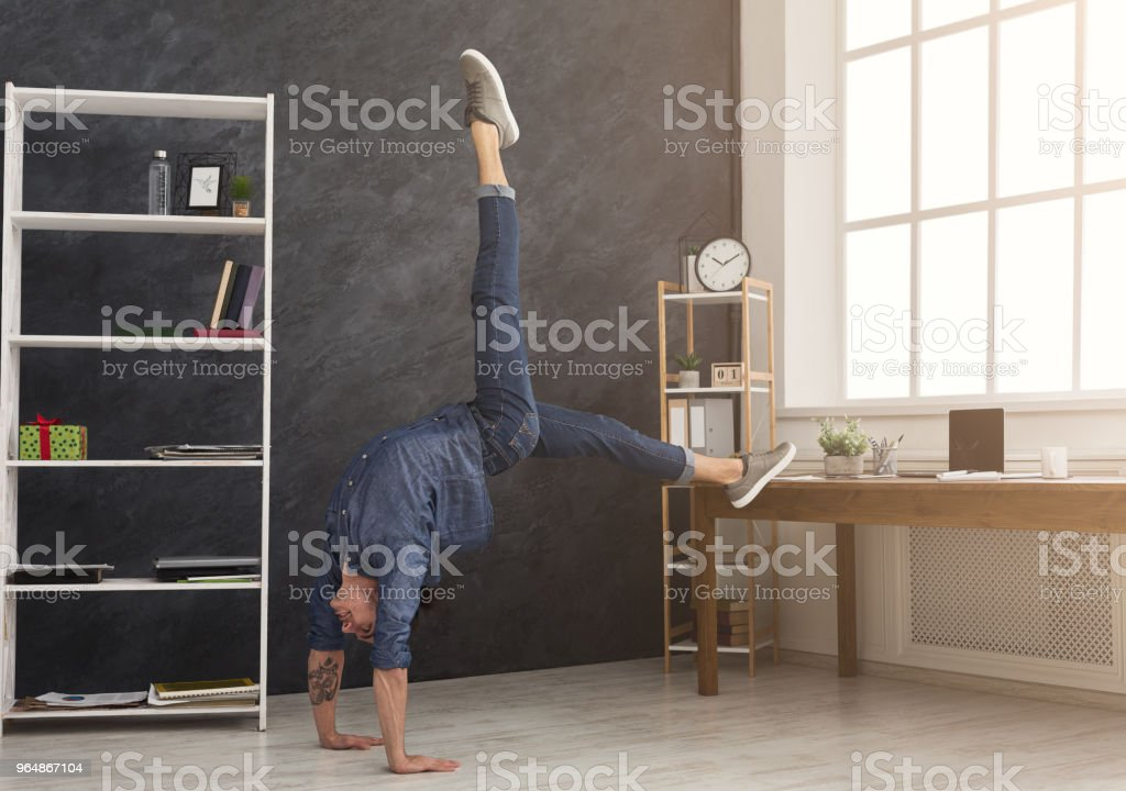Flexible man practicing yoga at workplace royalty-free stock photo