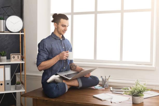 flexible man practicing yoga at workplace - poprawna postawa zdjęcia i obrazy z banku zdjęć
