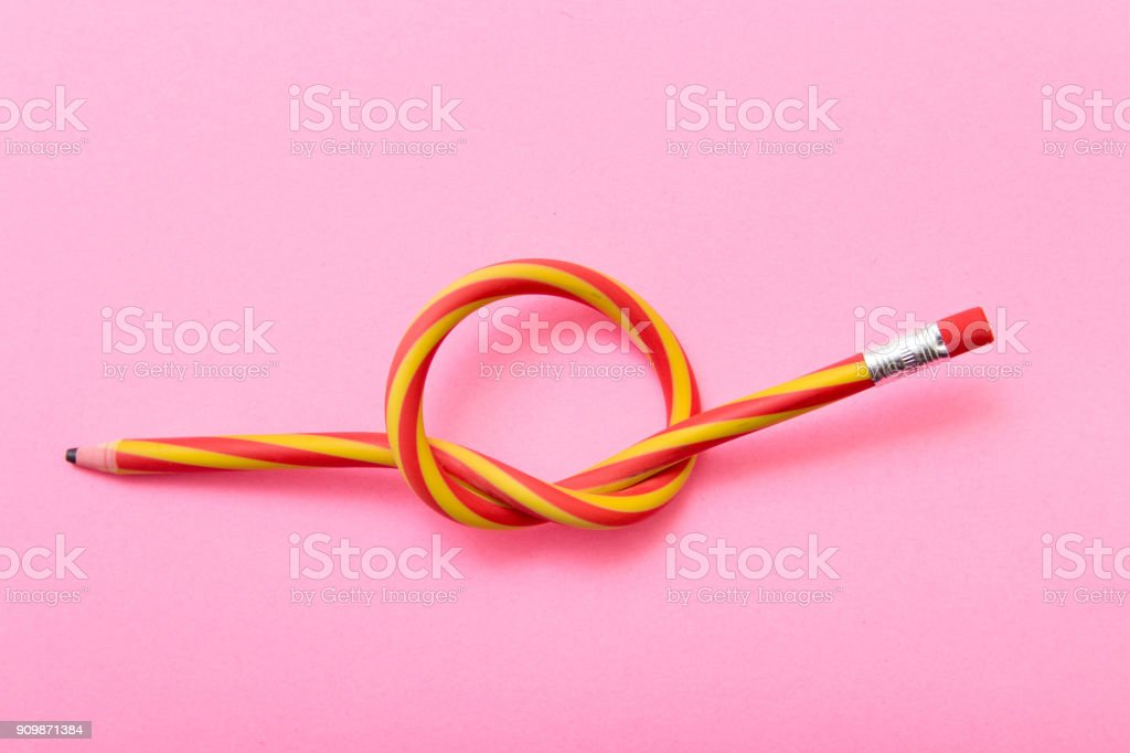 Flexible pencil on a pink background. Bent pencils two-color stock photo