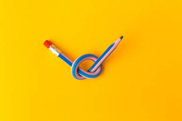 Flexible pencil on a yellow background. Bent pencils two-color. Business concept stock photo