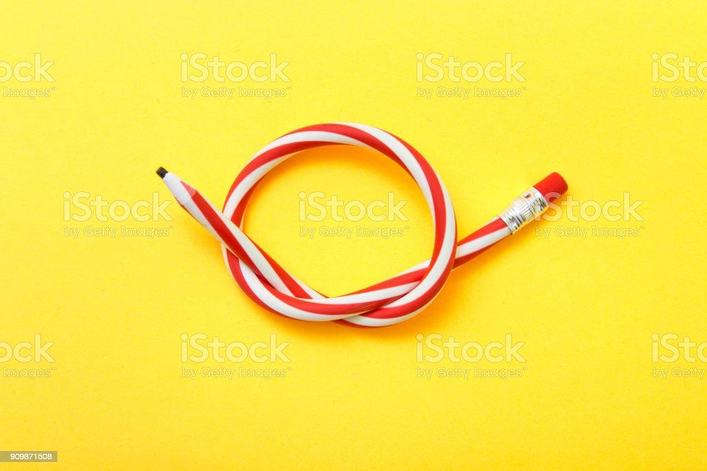 Lápis flexível sobre um fundo amarelo. Lápis dobrados duas cores - foto de acervo