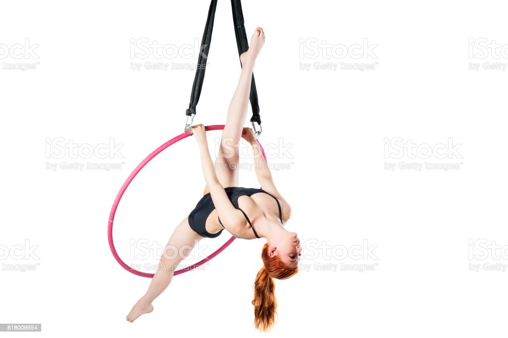 Flexible slender girl exercising in an air ring on a white background stock photo