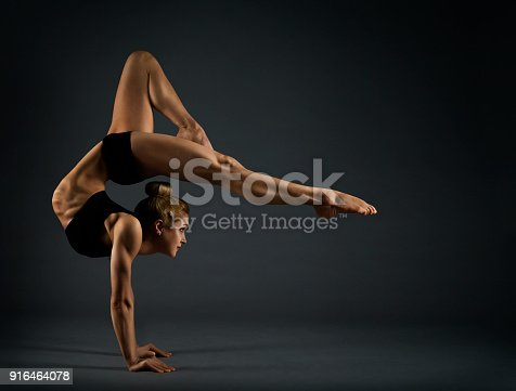 istock Flexible Woman Circus Gymnast, Gymnastics Hand Stand, Young Acrobat Standing on Hands, Yoga in Black Headstand Exercise 916464078