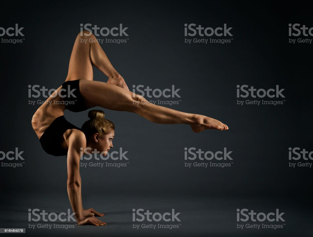 Flexible Woman Circus Gymnast, Gymnastics Hand Stand, Young Acrobat Standing on Hands, Yoga in Black Headstand Exercise stock photo