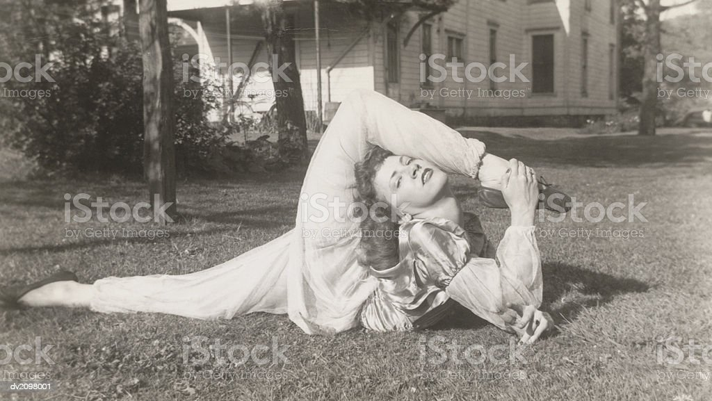 Flexible Woman in a Garden Bending Her Leg Above Her Head 免版稅 stock photo