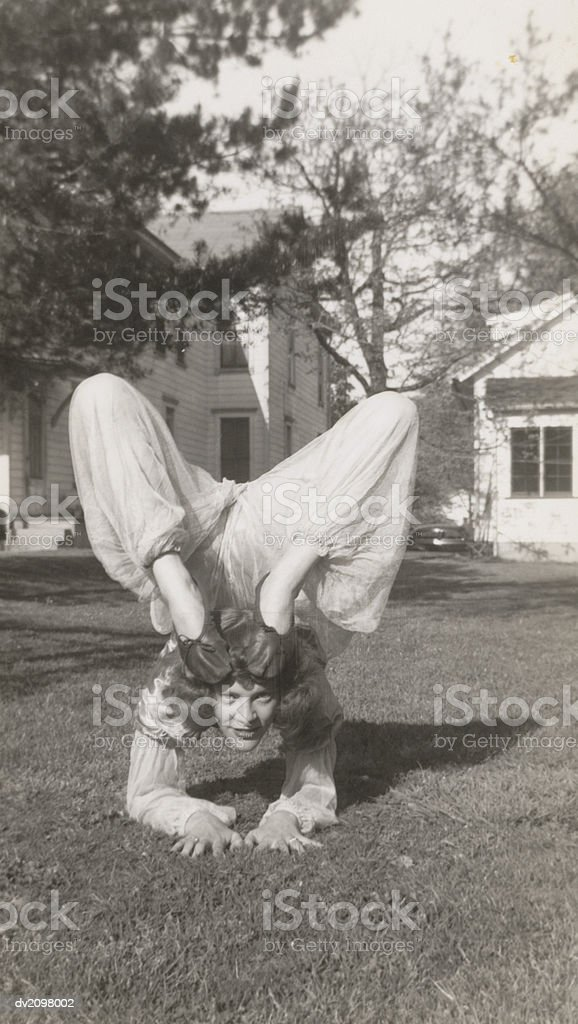 Flexible Woman in a Garden Bending Her Legs Above Her Head royalty-free stock photo