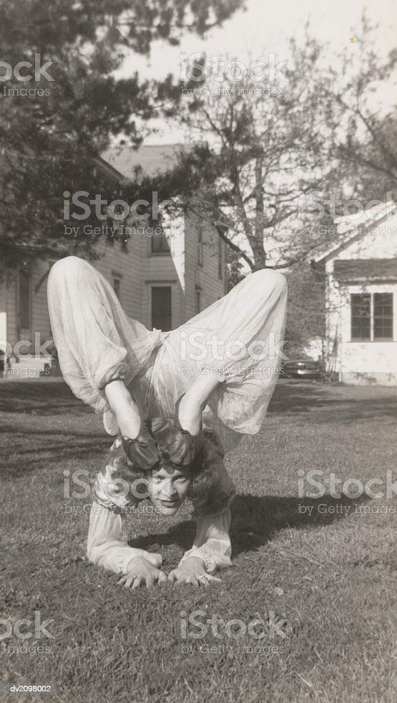Flexible Frau in einem Garten beugen Ihre Beine hoch über dem Kopf Lizenzfreies stock-foto