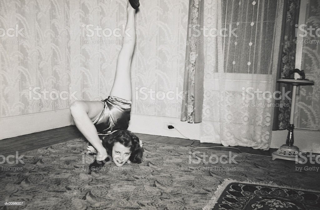 Flexible Woman on the Living Room Floor With Her Leg Over Her Head 免版稅 stock photo