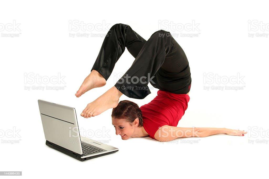 Flexible yogi lady using laptop with her feet stock photo