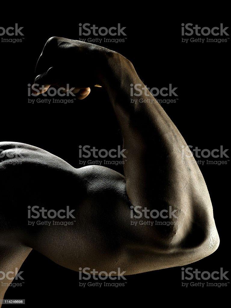 Flexing arm on black background royalty-free stock photo