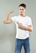 Portrait of confident young man wearing white t-shirt flexing his bicep. Studio shot, gray background.