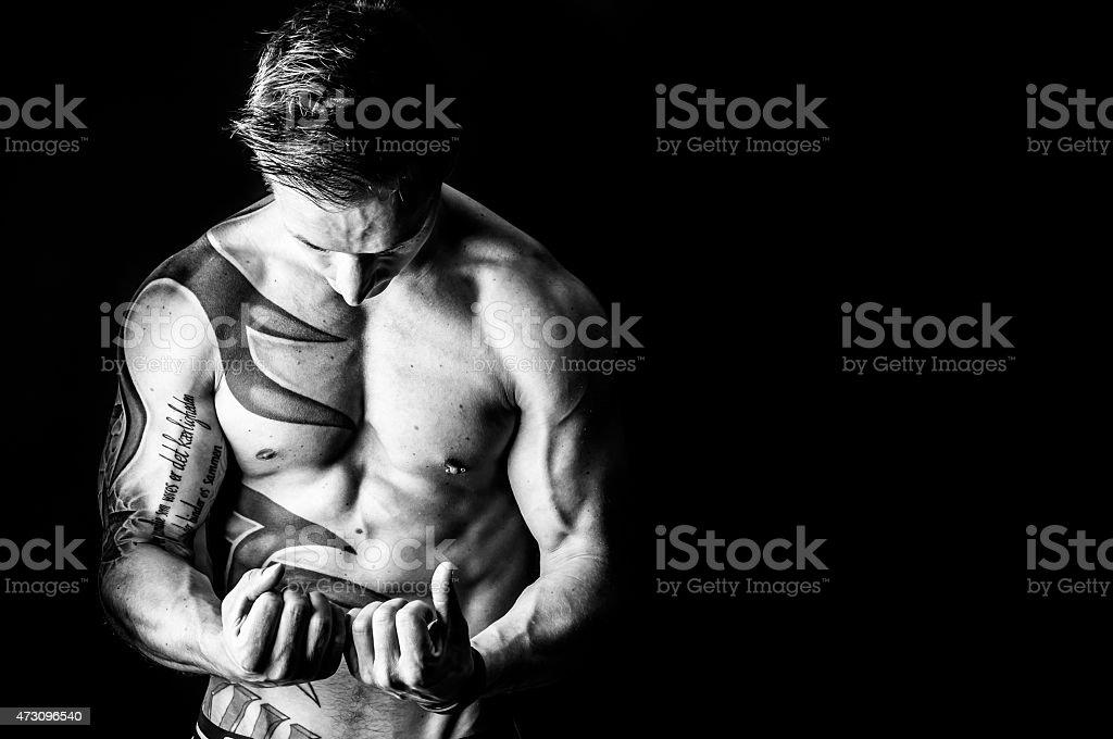 Flexing muscle tattood guy stock photo