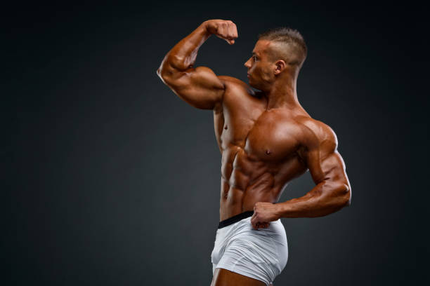 Flexing Muscles Young Body Builder Flexing Muscles bicep stock pictures, royalty-free photos & images