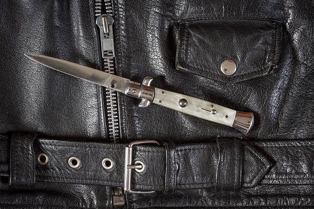 Flick knife on leather jacket Opened flick knife on a black leather jacket with zip, belt and pocket. switchblade stock pictures, royalty-free photos & images