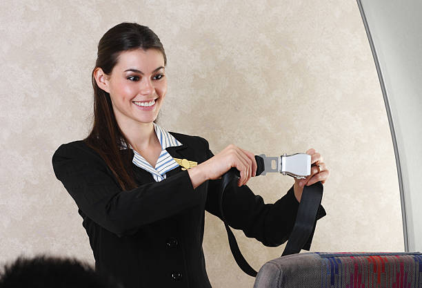 flight attendant and seat belt - gchutka stock pictures, royalty-free photos & images