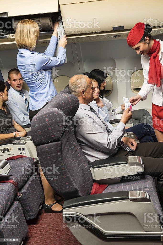 Flight attendant check passenger tickets cabin stock photo