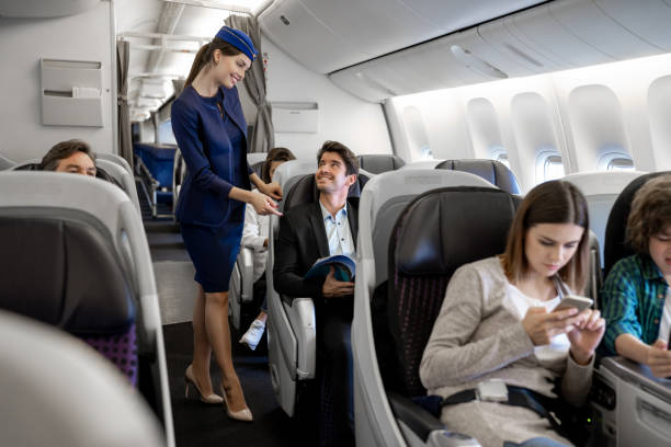 Flight attendant checking on a man in the airplane Portrait of a happy flight attendant checking on a man in the airplane air stewardess stock pictures, royalty-free photos & images