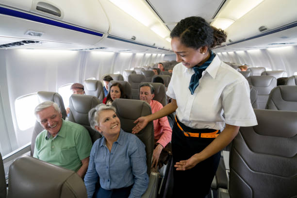 Flight attendant checking on a senior couple in an airplane Friendly flight attendant checking on a senior couple in an airplane and looking happy - travel concepts cabin crew stock pictures, royalty-free photos & images