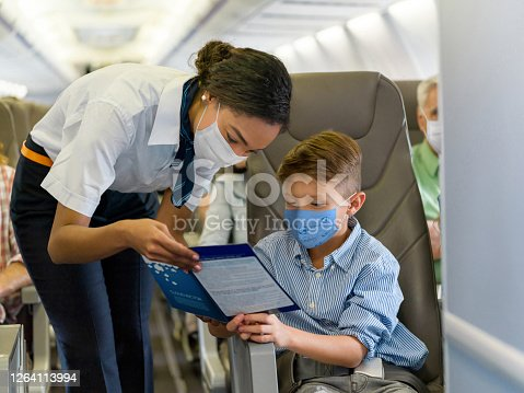 Friendly flight attendant helping a boy in an airplane and both wearing a facemask - travel during the COVID-19 pandemic concepts