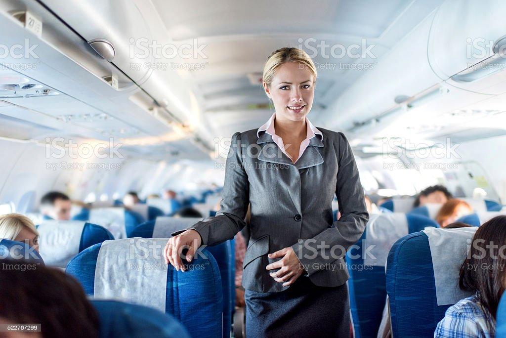 Flight attendant in airplane. stock photo