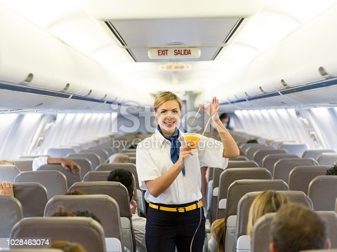 Portrait of a beautiful flight attendant making an in-flight safety demonstration and showing how to put the oxygen mask