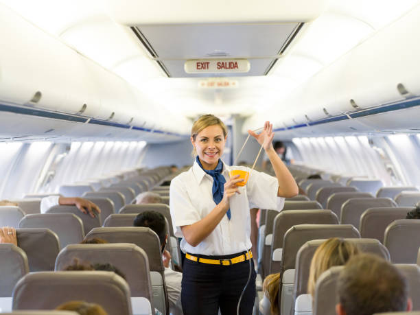 Flight attendant making an in-flight safety demonstration Portrait of a beautiful flight attendant making an in-flight safety demonstration and showing how to put the oxygen mask cabin crew stock pictures, royalty-free photos & images