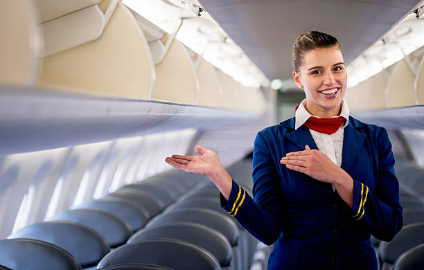 Flight attendant Friendly flight attendant gesturing in an airplane cabin crew stock pictures, royalty-free photos & images
