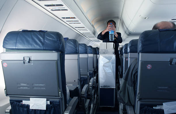 Flight Attendant A flight attendant on the job, in a small plane. cabin crew stock pictures, royalty-free photos & images