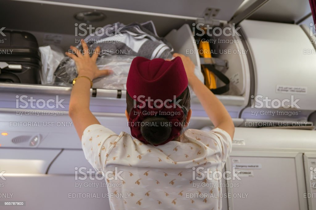 Flight Attendant Putting Luggage Into Overhead Locker On Qatar Airways  Aircraft Stock Photo - Download Image Now