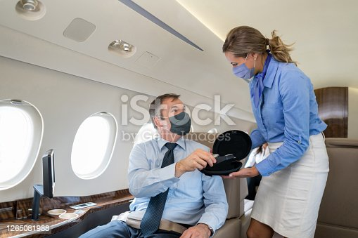 First class flight attendant serving passenger in an airplane and both wearing facemasks – COVID-19 pandemic lifestyle concepts