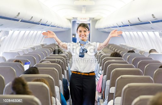 Portrait of a beautiful flight attendant showing the emergency exit in an airplane before takeoff - travel concepts