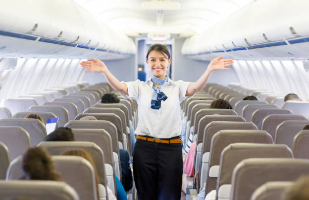 Flight attendant showing the emergency exit in an airplane Portrait of a beautiful flight attendant showing the emergency exit in an airplane before takeoff - travel concepts cabin crew stock pictures, royalty-free photos & images
