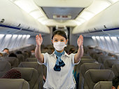 Portrait of a flight attendant showing the emergency exit in an airplane wearing a facemask before takeoff - traveling during the pandemic concepts