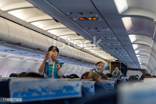 SUVANNABHUMI AIRPORT, BANGKOK, THAILAND - MARCH 23, 2019 : Flight attendants demonstrate the proper use of oxygen masks before flight