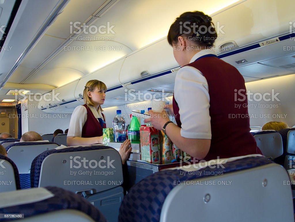 Flight attendants serve passengers of UT-578 airlines UTair stock photo