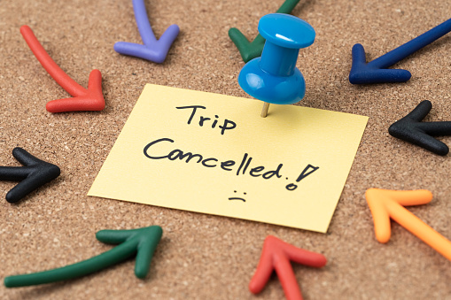 Flight cancelled due to COVID-19 virus spread outbreak, cancel plan to travel reminder concept, Thumbtack pushpin with multi arrows pointing to small paper note written the word Trip Cancelled