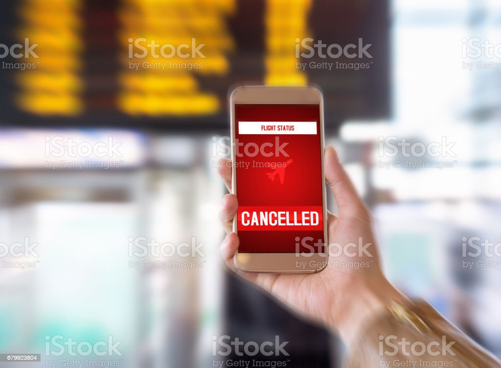 Flight cancelled. Smartphone application announces bad news to tourist. Strike or problem with plane. Woman holding mobile phone in airport terminal. Timetable and schedule in the blurred background. stock photo