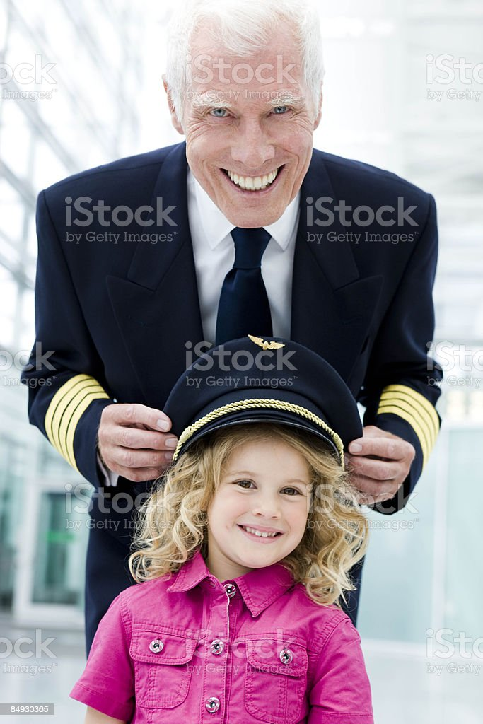 Flight captain fitting hat onto girl royalty-free stock photo