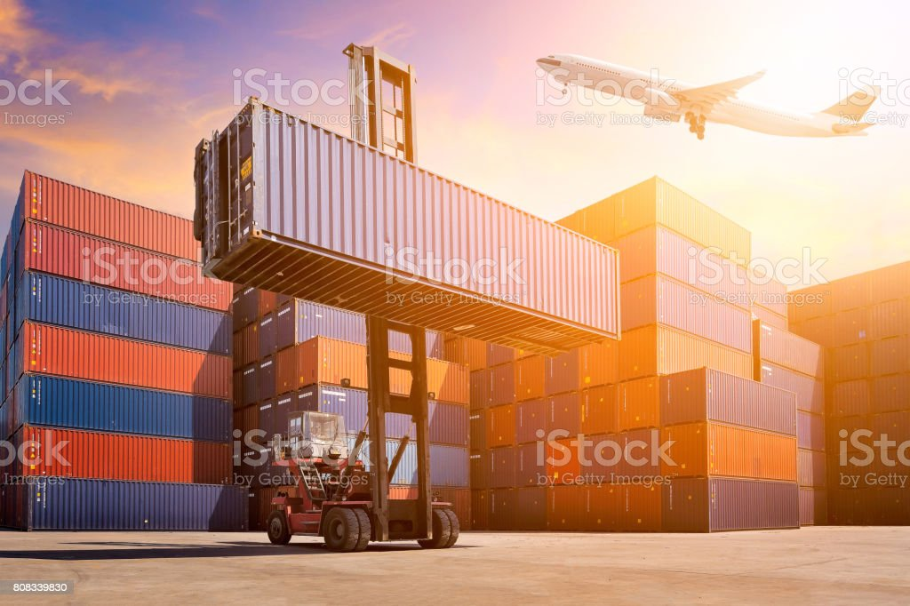 Flight cargo flying over Logistic cargo container in shipping yard. stock photo