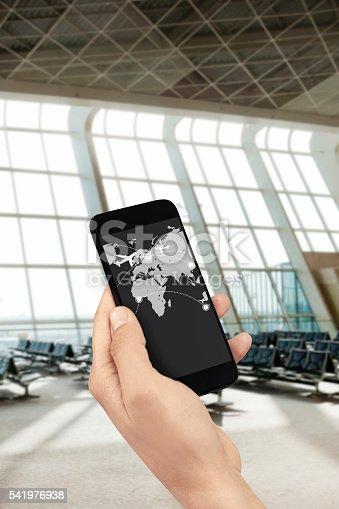 hand holding a mobile phone in an airport departure lounge in Heydar Aliyev International Airport,Baku,Azerbaijan.