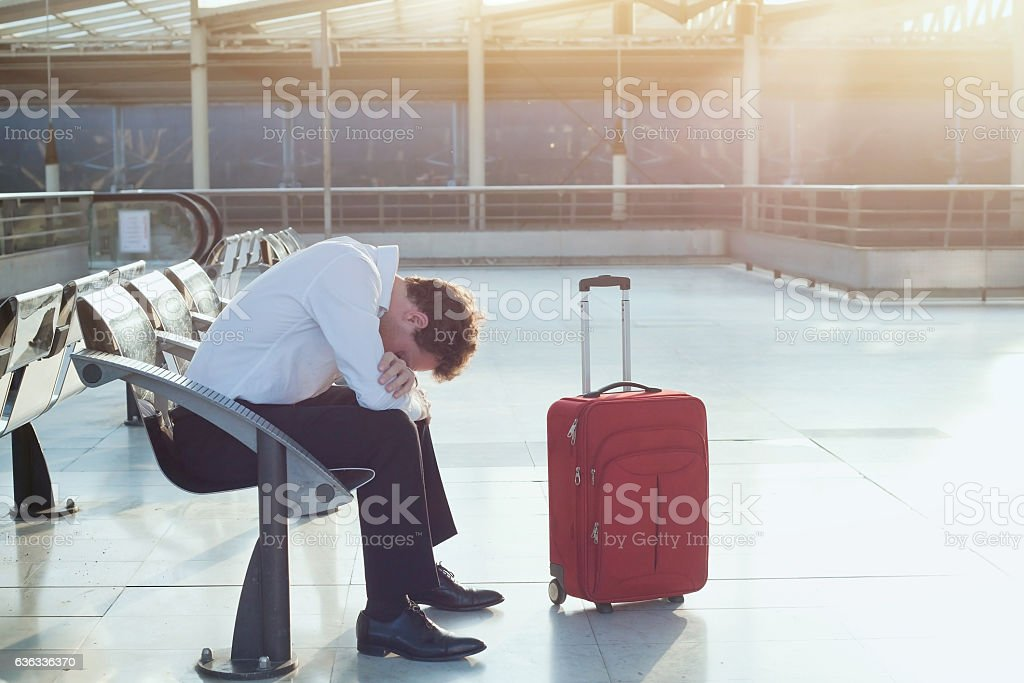 flight delay in airport, tired troubled man with luggage stock photo